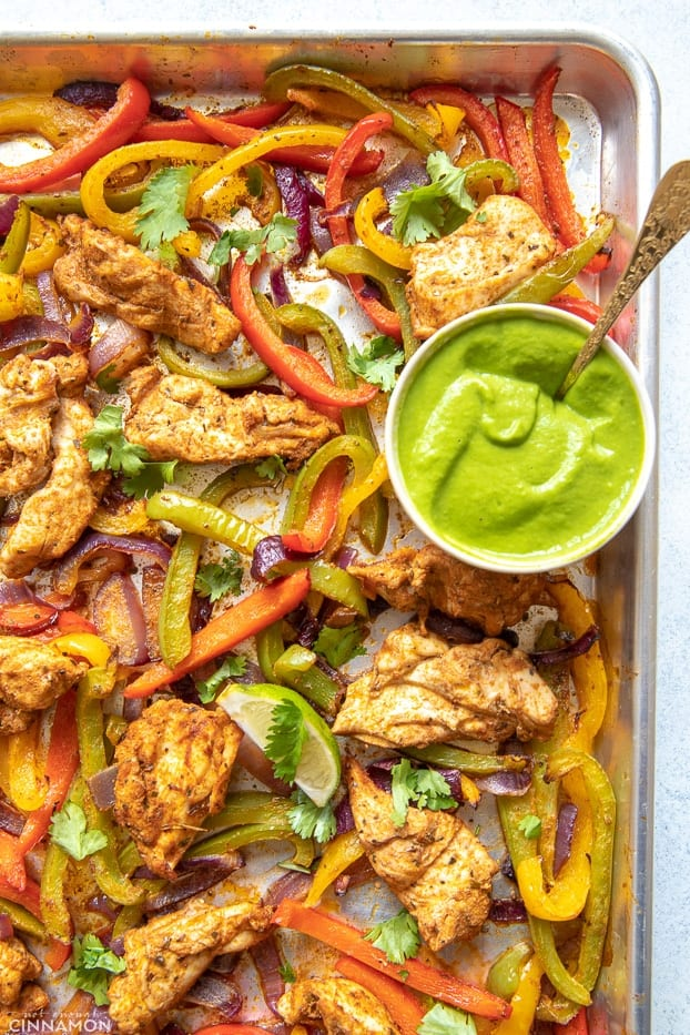 overhead shot of a sheet pan with low carb healthy oven baked chicken fajitas with a side dish containing creamy avocado sauce