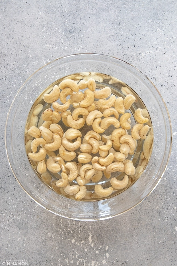 overhead shot of a big glass bowl with raw cashew nuts soaking in cold water
