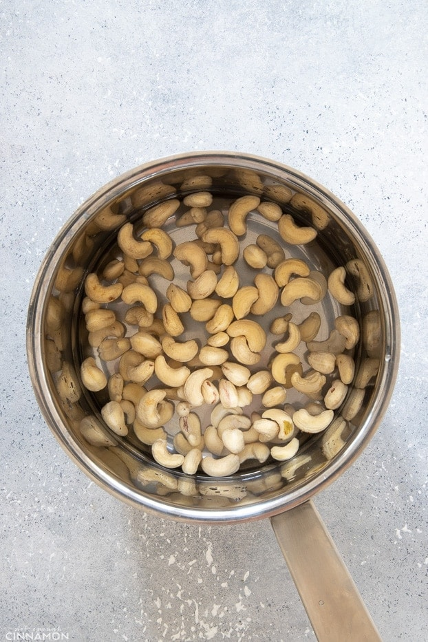 overhead shot of a silver pot with cashew nuts covered with cold water
