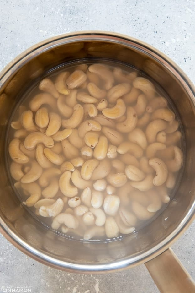 overhead shot of cashew nuts soaking in hot water in a sliver pot