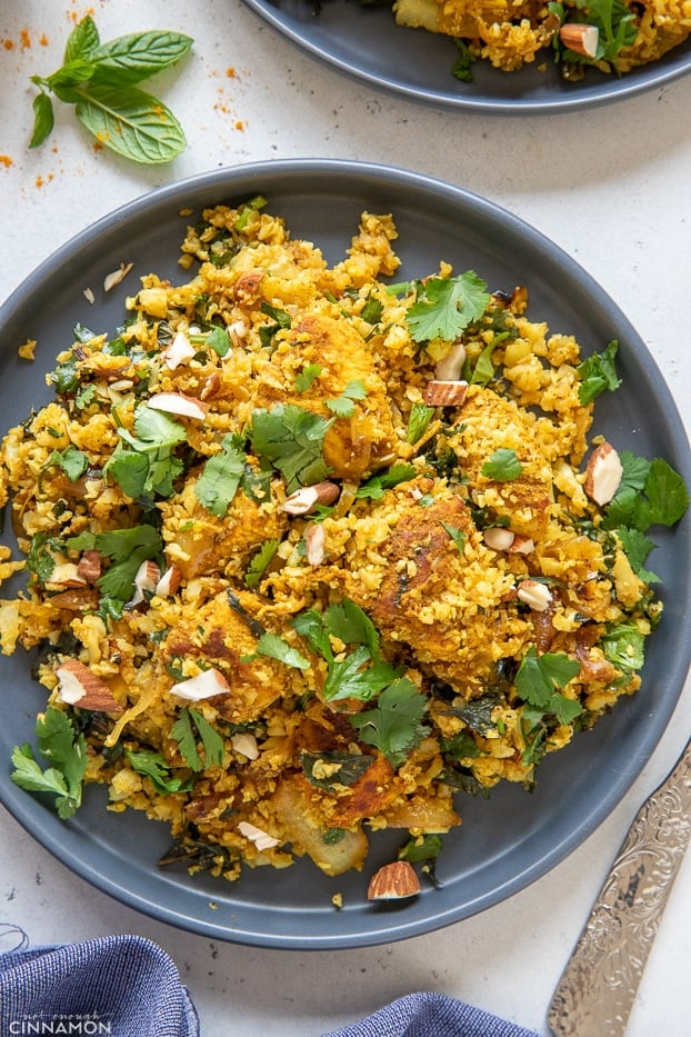 overhead shot of a blue plate with Indian paleo cauliflower rice stir-fry with chicken