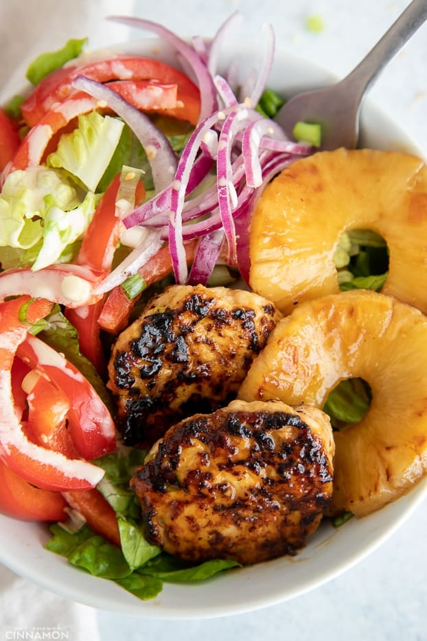 overhead close-up of a healthy Hawaiian chicken burger bowl with juicy chicken patties and charred pineapple rings