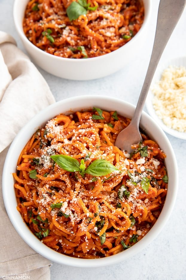 overhead shot of sweet potato noodles with Italian tomato sauce in a white bowl