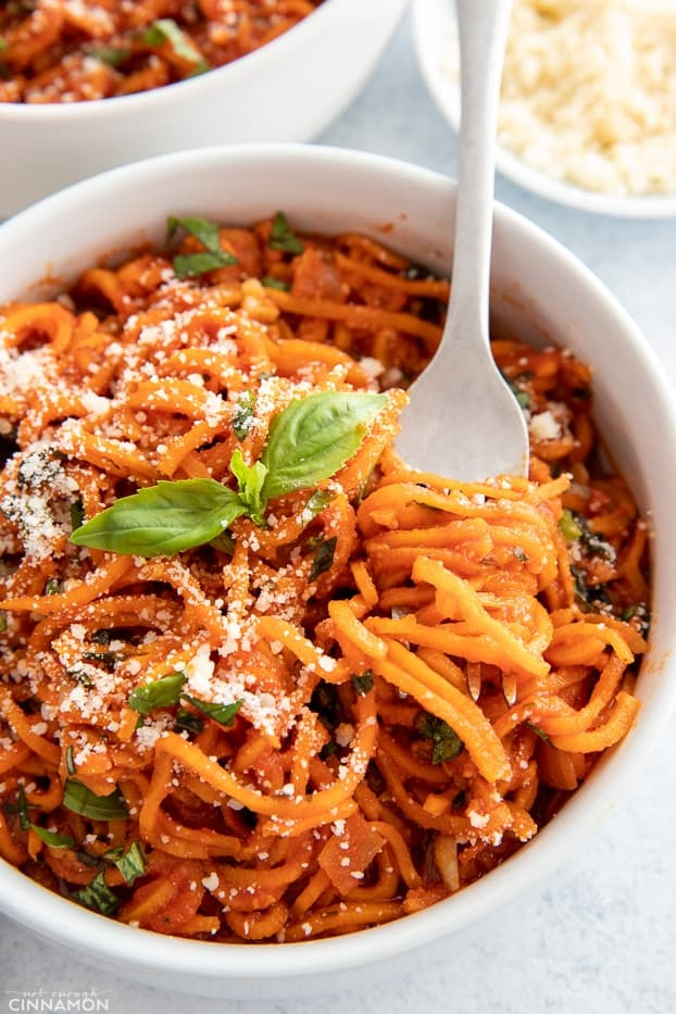 a fork twirling sweet potato spaghetti with tomato sauce in a white pasta bowl