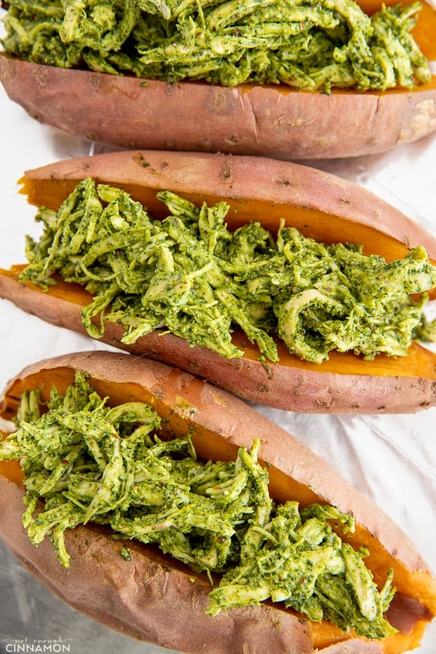 overhead shot of three baked stuffed sweet potatoes filled with dairy-free basil pesto chicken