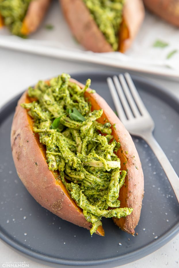 a paleo pesto chicken stuffed baked sweet potato on a black plate with a fork