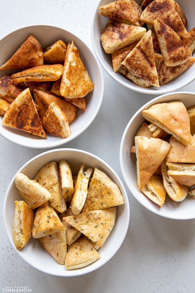 overhead shot of 4 different kinds of homemade pita chips in white bowls