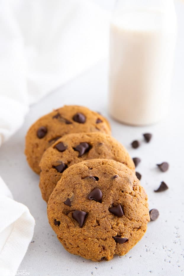 three healthy protein cookies with chocolate chips and a glass of milk in the background