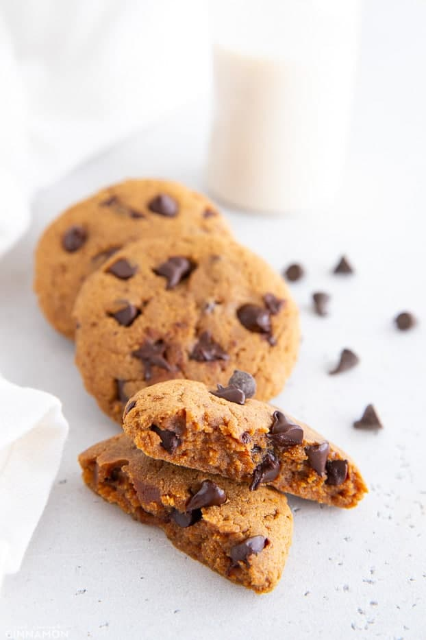healthy 5 ingredient protein cookies with dark chocolate chips and a glass of milk in the background