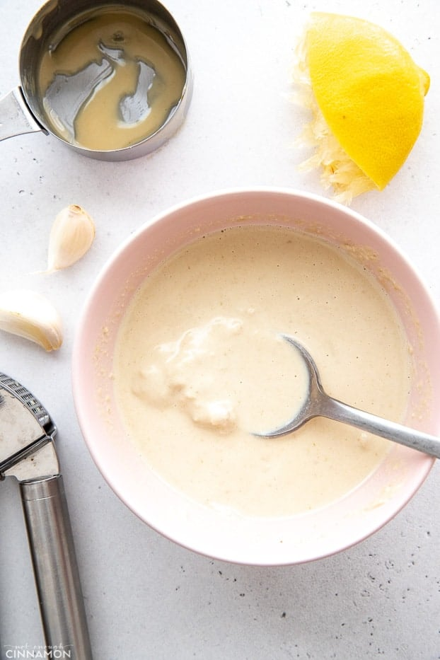 overhead shot of a bowl of homemade tahini sauce with ingredients surrounding the bowl