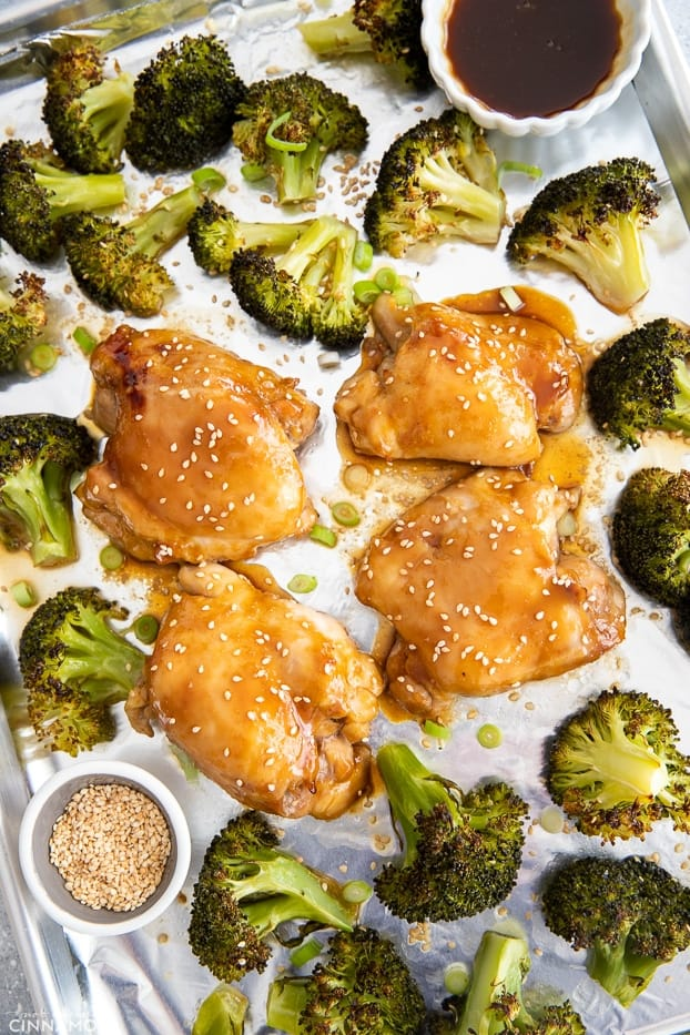 overhead shot of sheet pan chicken thighs with teriyaki glaze and broccoli on a sheet pan