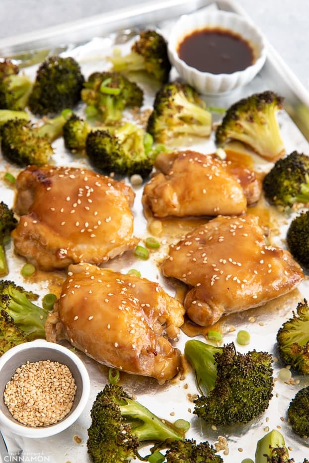 sesame sprinkled Asian glazed Teriyaki chicken thighs with broccoli on a sheet pan
