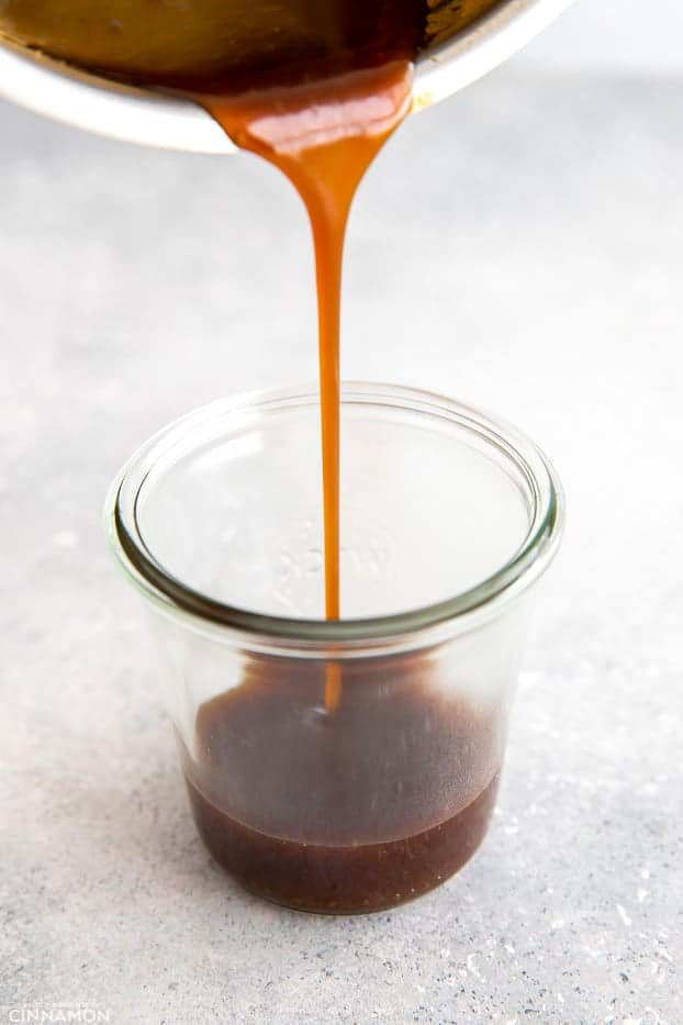 homemade healthy Whole30 teriyaki sauce being poured from a saucepan into a jar