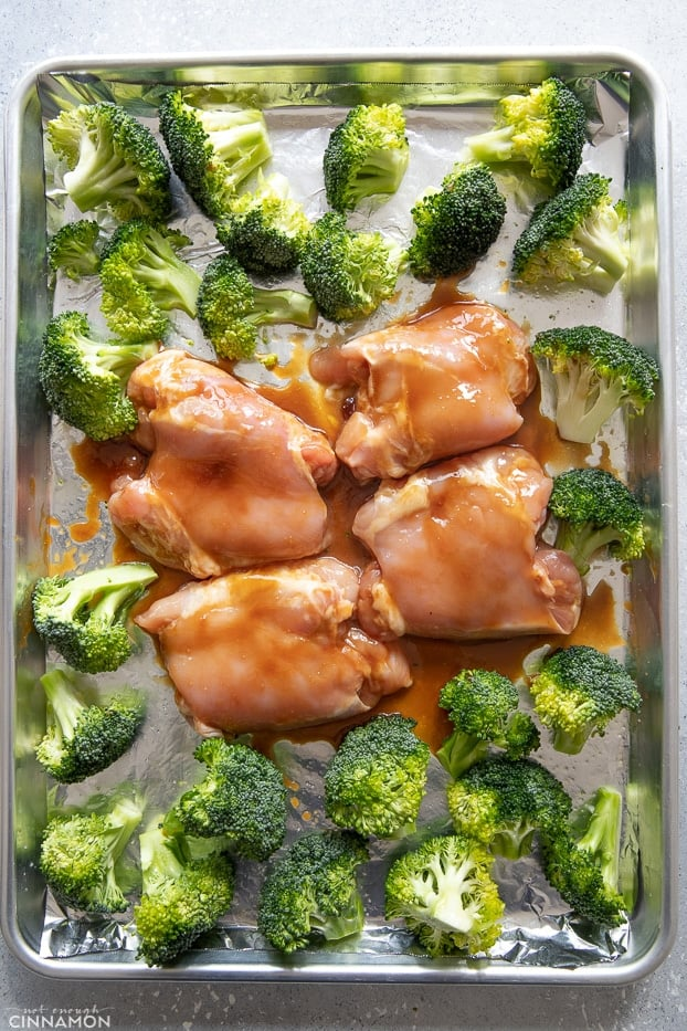 raw Teriyaki glazed chicken thighs surrounded with broccoli florets on a baking pan