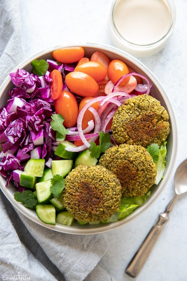 overhead shot of a healthy falafel bowl with a side dish of tahini sauce