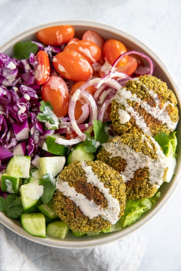 healthy baked falafel bowl drizzled with homemade tahini sauce