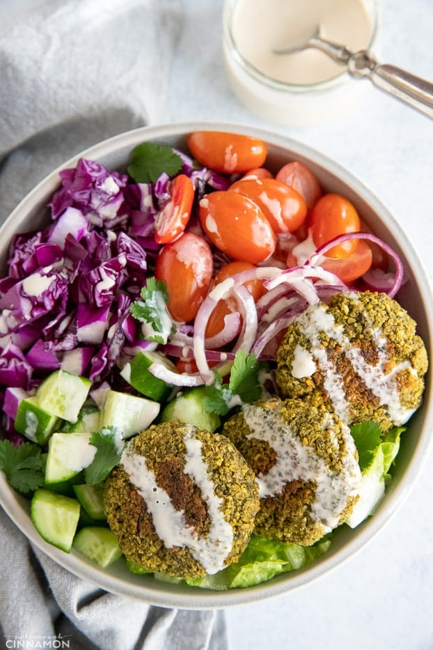 overhead shot of a healthy baked falafel bowl drizzled with tahini sauce