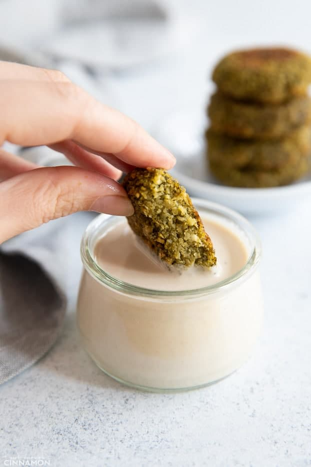 a baked falafel patty being dipped into a small glass jar of homemade tahini sauce