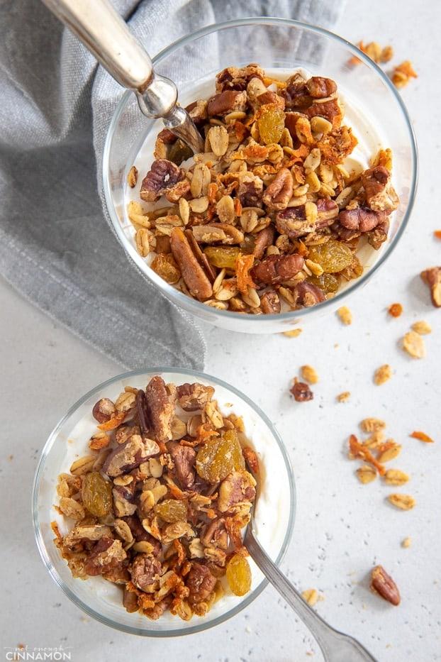 overhead shot of two dessert glasses layered with vegan carrot cake granola and yogurt