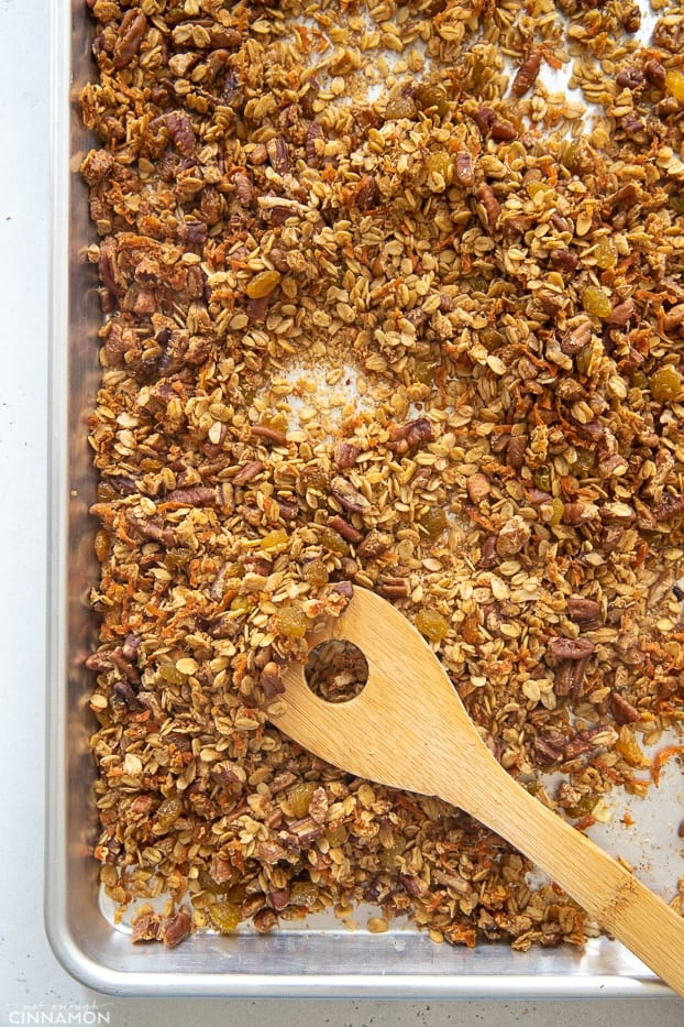 a wooden spoon stirring homemade gluten-free carrot cake granola on a sheet pan