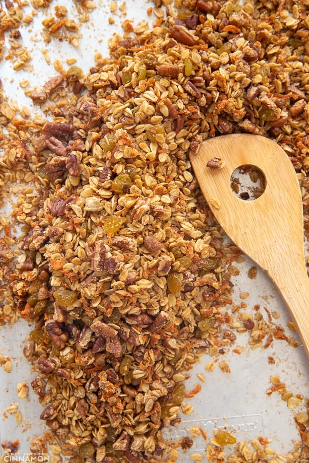 overhead shot of a sheet pan with healthy carrot granola being stirred with a wooden spoon