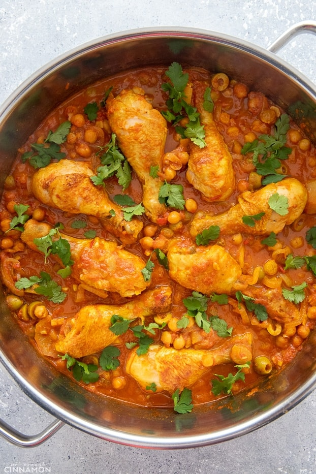 overhead shot of a pot filled with Moroccan chicken drumsticks simmered with chickpeas, raisins and lemon