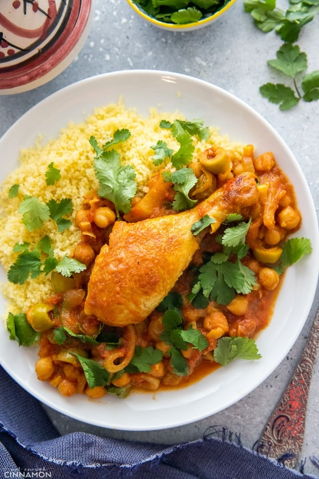 overhead shot of a serving of Moroccan chicken tagine served with a side of fluffy couscous and chickpeas