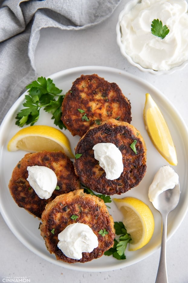 overhead shot of healthy gluten-free salmon patties served with dollops of sour cream and lemon wedges