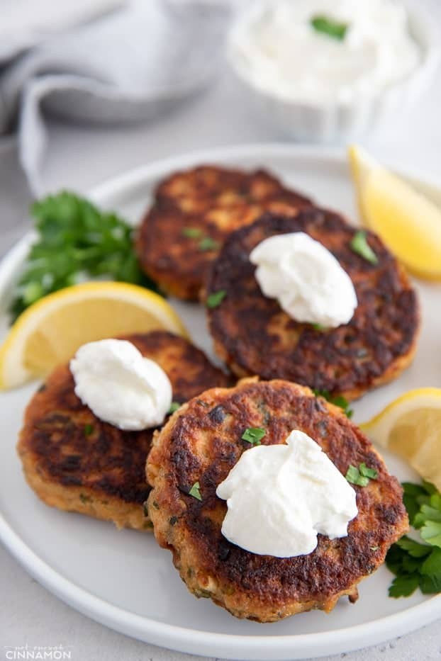healthy whole30 salmon patties on a white plate topped with sour cream