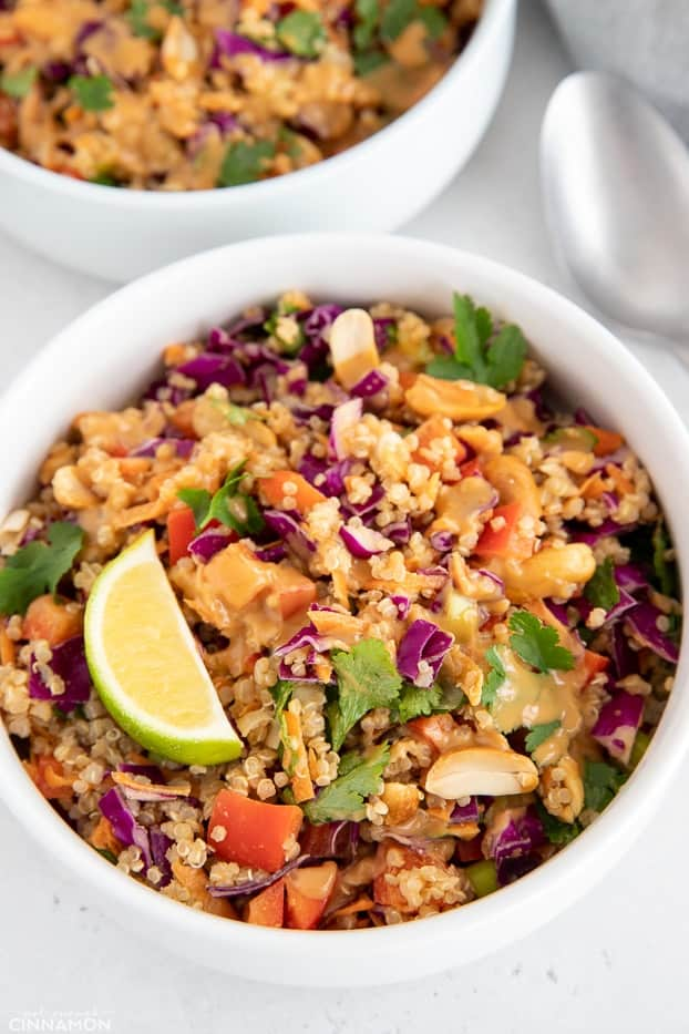 close-up of a bowl of Thai Quinoa Salad decorated with lime slices and cilantro and drizzled with Peanut Dressing