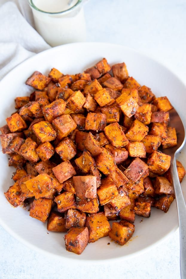 overhead shot of a white bowl with roasted sweet potato cubes with caramelized edges
