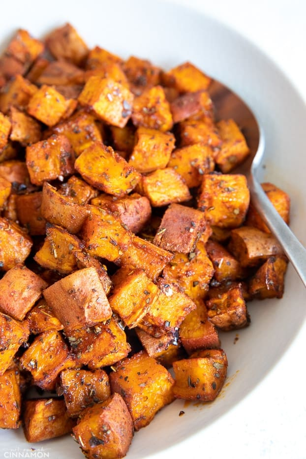 side view of oven perfect cubes of roasted sweet potatoes served in a white bowl