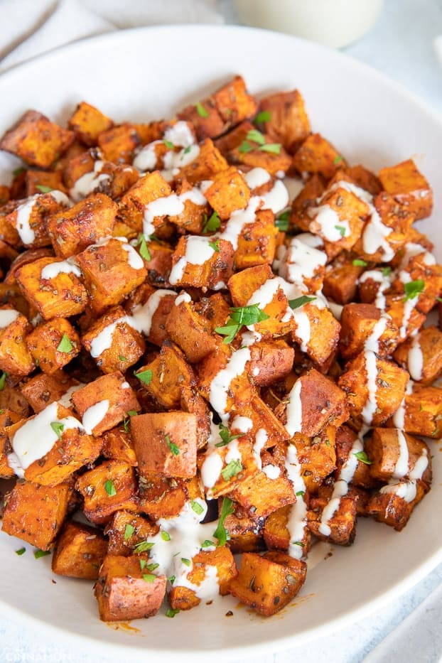 roasted sweet potato cubes on a white plate drizzled with tahini sauce