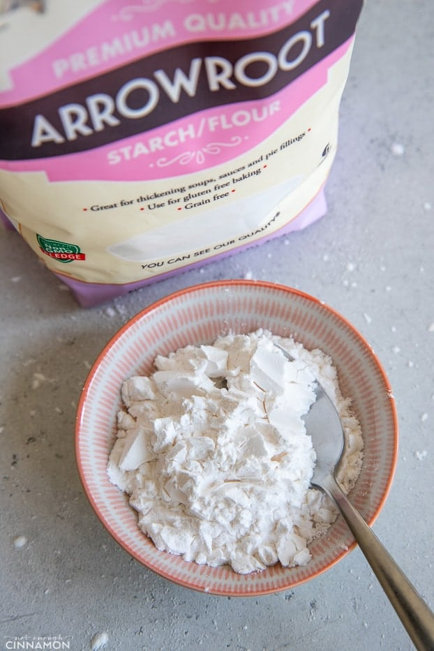 a small bowl of arrowroot starch next to a bag of premium arrowroot powder