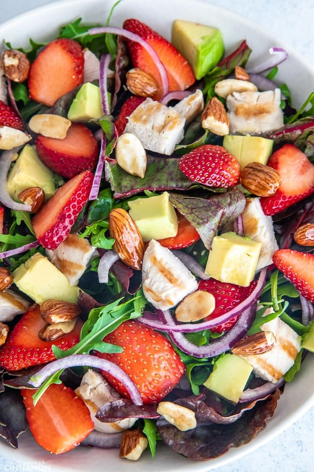 overhead shot of healthy chicken salad with candied almonds, avocado and strawberries