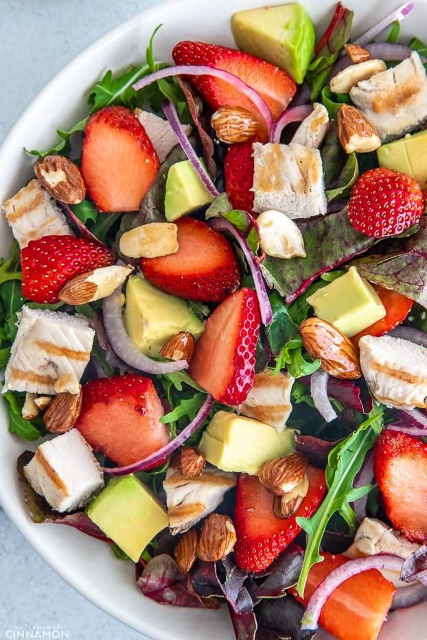 overhead shot of a healthy chicken salad with candied almonds, strawberries and avocado