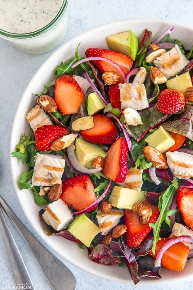 overhead shot of a big bowl with strawberry chicken salad with almonds and avocados with creamy poppy seed dressing in the background