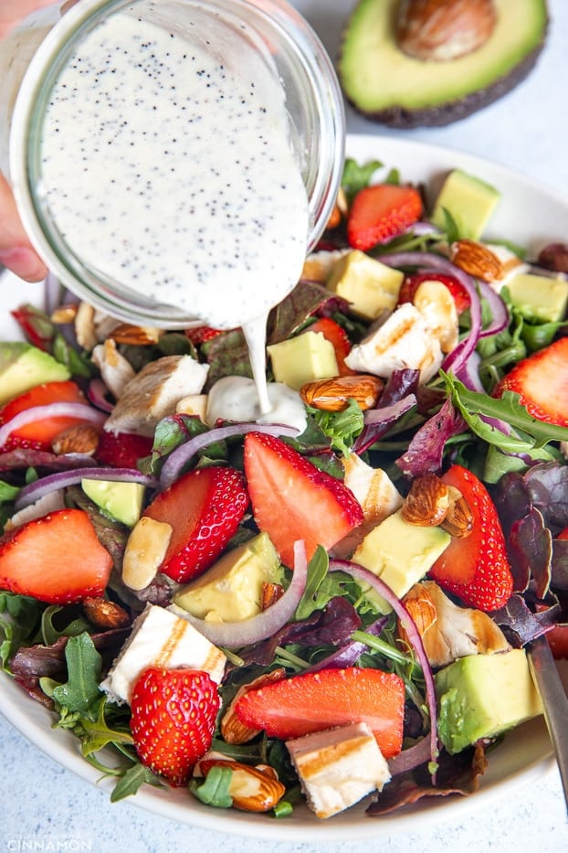 creamy lemon poppy seed dressing being poured on top of healthy strawberry chicken salad
