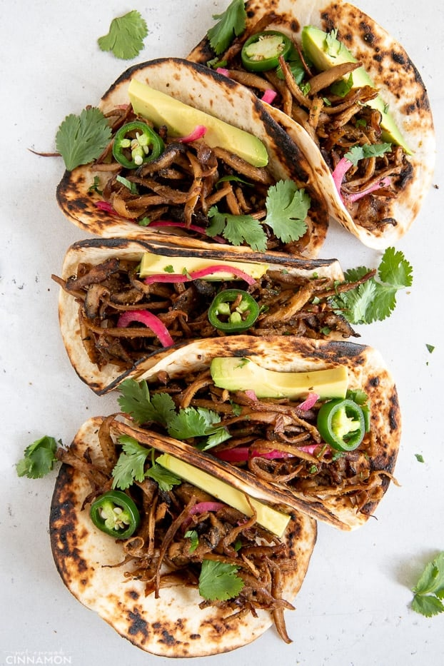 overhead shot of vegan mushroom carnitas tacos topped with Jalapeno and cilantro leaves
