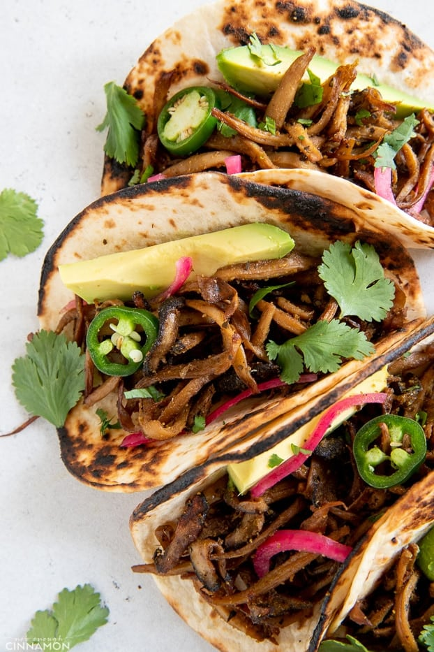 overhead shot of vegan mushroom carnitas tacos tipped with cilantro, quick pickled onions and avocado