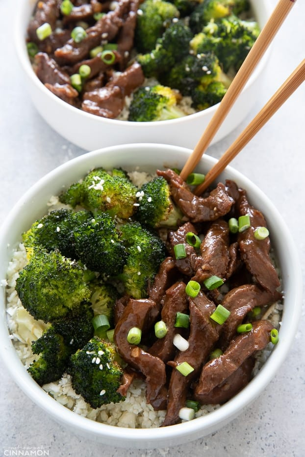 a bowl of Mongolian Beef and Broccoli served over cauliflower rice with chopsticks on the side