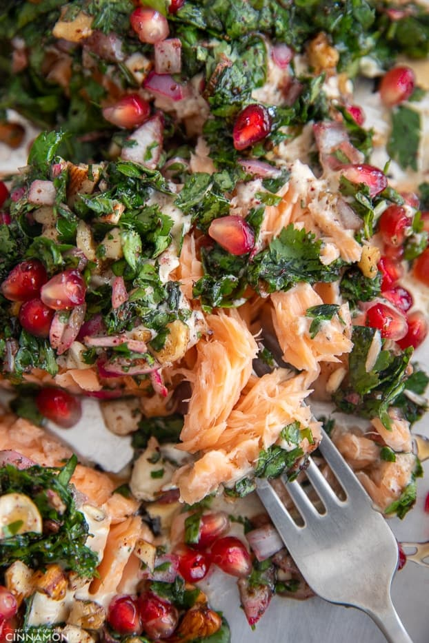 a fork taking a bite out of an oven baked salmon fillet topped with herbs and pomegranate seeds