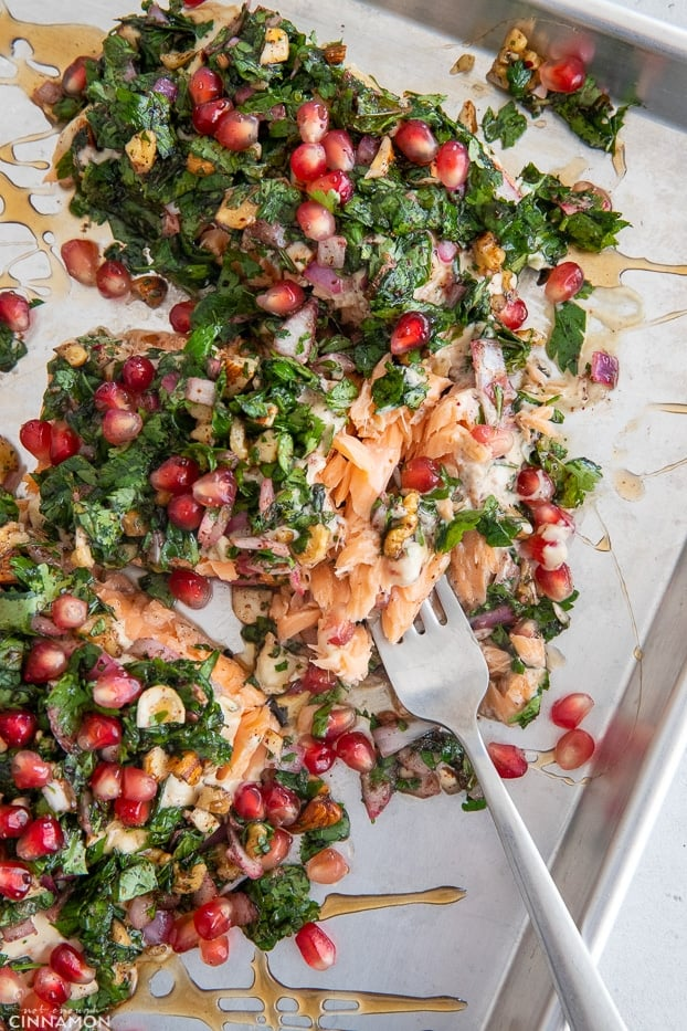 a fork tucking into a baked salmon fillet covered with herbs and pomegranate seeds