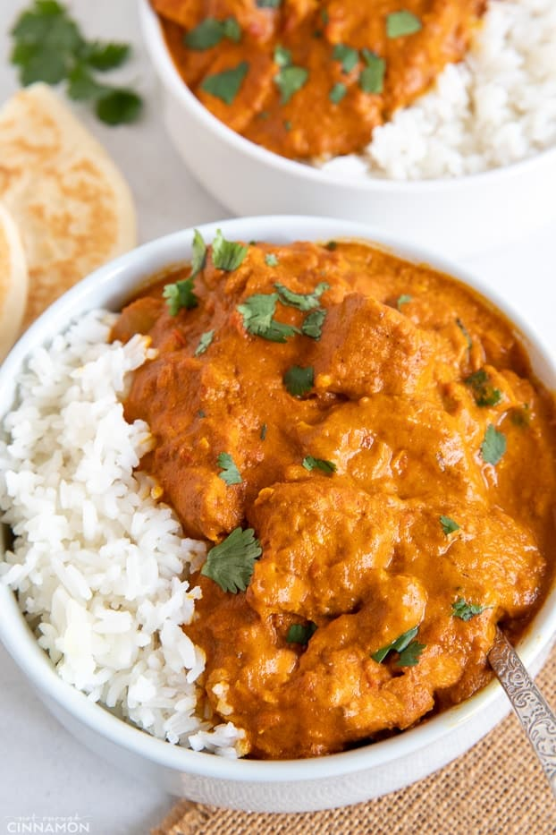 a serving of healthy dairy-free paleo slow cooker butter chicken served with rice and fresh cilantro