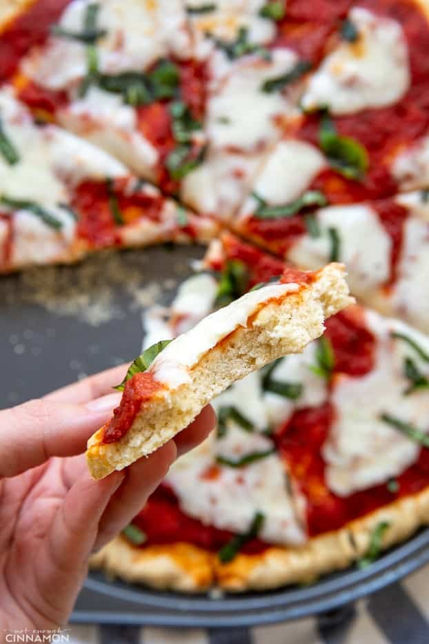 a hand holding a cheesy slice of paleo Pizza Margherita