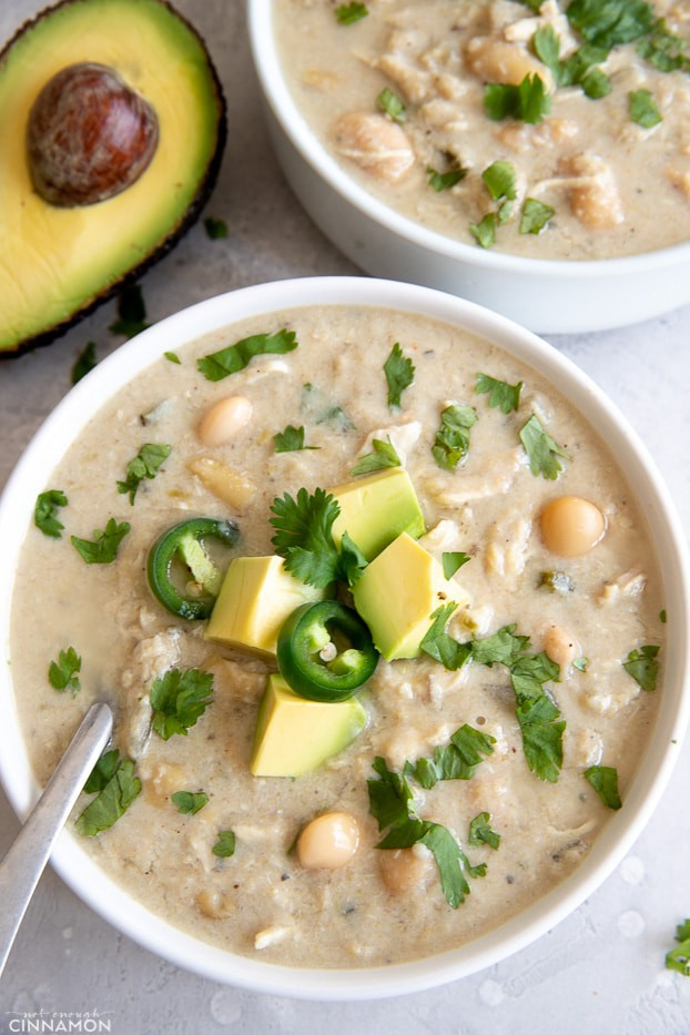 overhead shot of a bowl of slow cooker white chicken chili topped with avocado and cilantro leaves