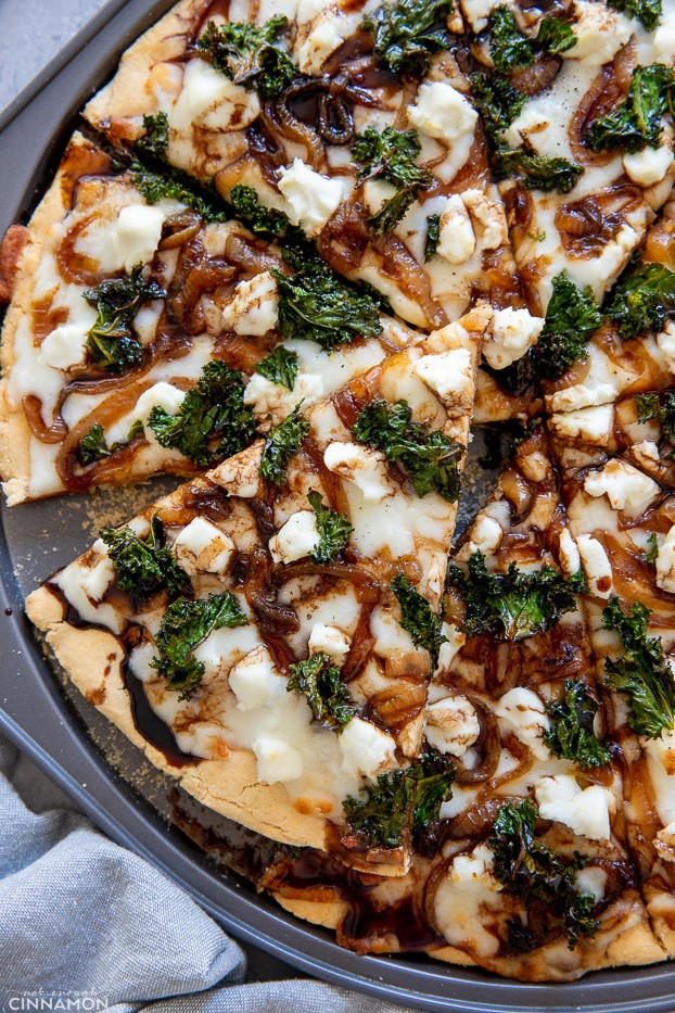close-uo overhead shot of a goat cheese and kale pizza drizzled with balsamic reduction