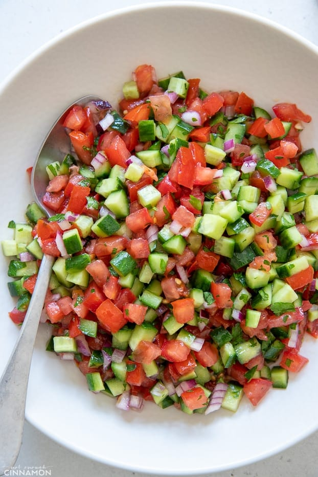 overhead shot of a plate of Israeli Salad with a spoon on the side