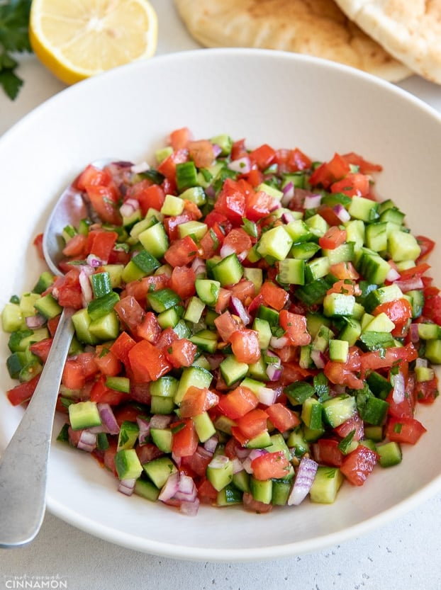 side view of a plate of chopped Israeli salad with a spoon on the side
