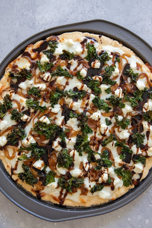 overhead shot of a kale pizza with caramelized onions and goat cheese drizzled with balsamic reduction
